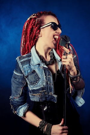 goth girl: Modern rock singer singing into a microphone. Stock Photo
