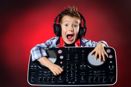 hardrock: Expressive little boy DJ in headphones mixing up some party music. Stock Photo