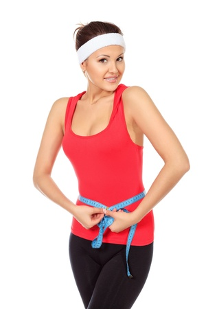 Slender young woman in sportswear measuring her waist. Isolated over white. photo