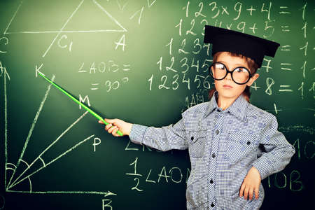 clever: Portrait of a boy in round glasses and academic hat standing near the blackboard in a classroom. Stock Photo
