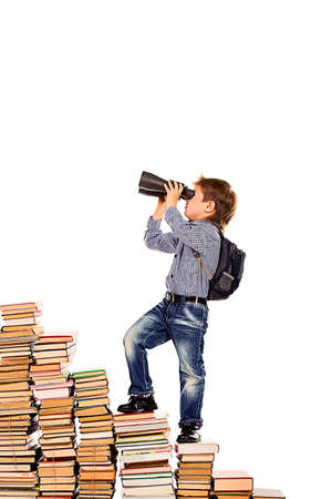 hard look: A boy climbing the stairs of books and looking into the distance through binoculars. Isolated over white.