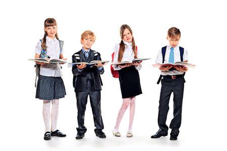 uniform school: Grupo de ni�os alegres de pie con libros. Aislado en blanco.