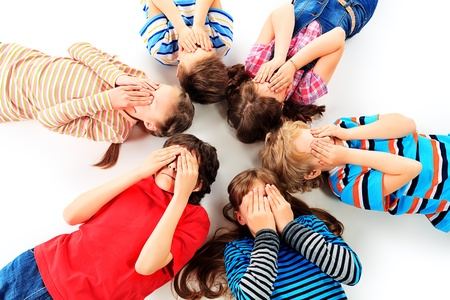floor covering: Group of children lying on a floor and covering their faces with their hands. Isolated over white. Stock Photo