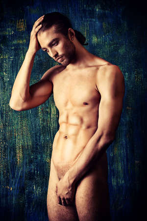 naked male body: Sexual muscular nude man posing over dark background. Stock Photo