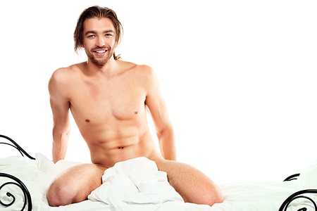 nude in bed: Handsome nude man sitting on a bed. Isolated over white. Stock Photo