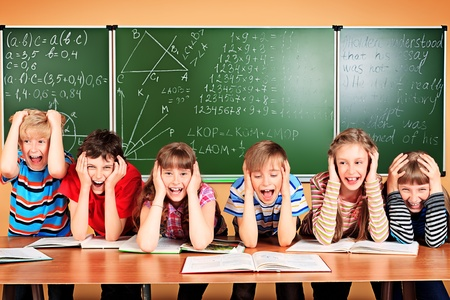 grabing: Group of tired school children at a classroom grabing their heads. Education.