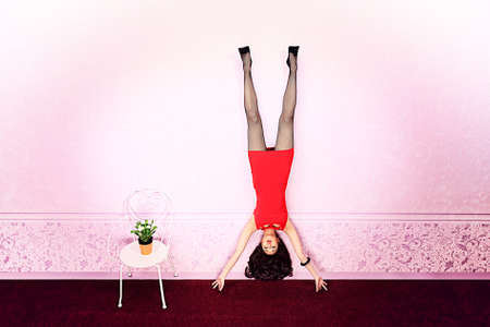 Fashionable young woman in a vivid red dress standing upside down in a pink room. photo