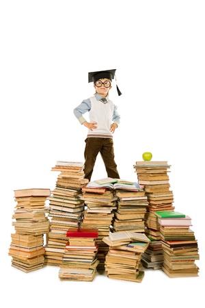 diligente: Un niño en el sombrero académico de pie sobre una pila de libros. Educación. Aislado en blanco.