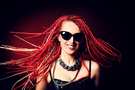 Portrait of expressive girl with great red dreadlocks. photo