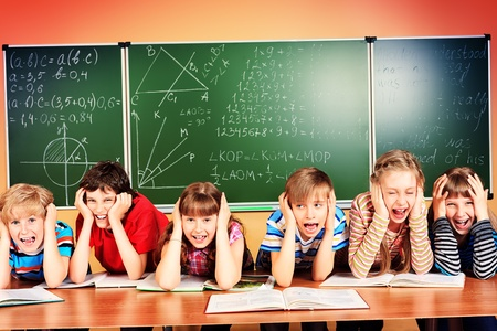 classmates: Group of tired school children at a classroom grabing their heads. Education.