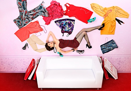 flying woman: Charming fashionable woman flying in the room, surrounded by lots of her clothes. Stock Photo