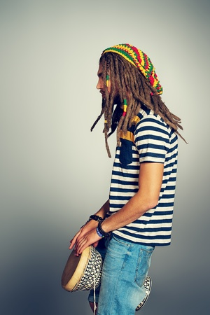 Portrait of a rastafarian young man playing his drum. Stock Photo