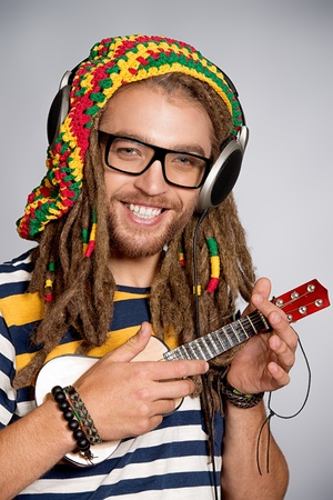 rasta: Portrait of a happy rastafarian young man playing his guitar. Stock Photo