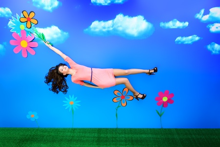 Romantic girl is flying through the sky on flowers. photo