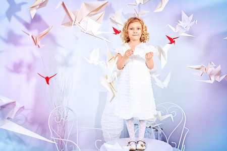 Beautiful little girl in her dream world surrounded with paper birds. Stock Photo - 21201030
