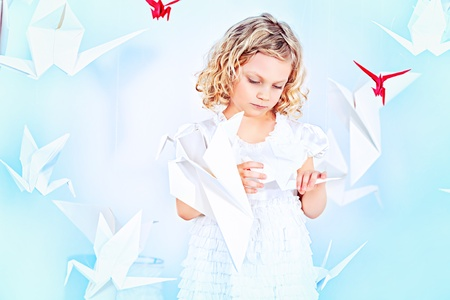 angelic: Beautiful little girl in her dream world surrounded with paper birds.