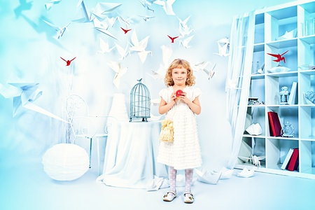 Beautiful little girl in her dream world surrounded with paper birds. Stock Photo - 21201121