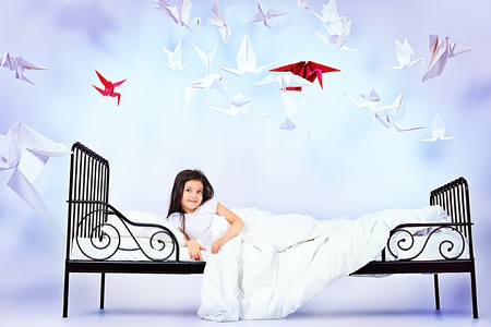 Pretty little girl lying in her bed surrounded by paper birds. Dream world. photo