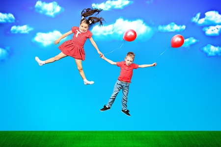 Two happy children flying together on balloons in a bright summer day. photo