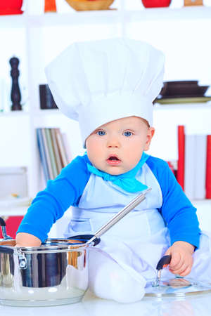 Cute small baby in the cook costume at the kitchen. photo