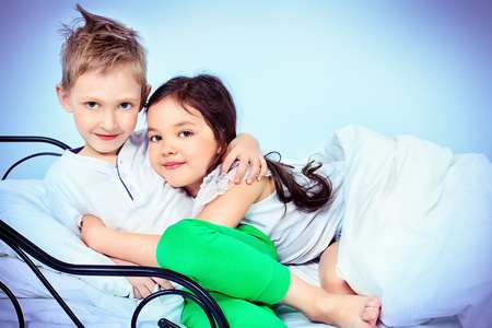 child in bed: Cute kids sitting together on the bed under the blanket. Dream world. Stock Photo