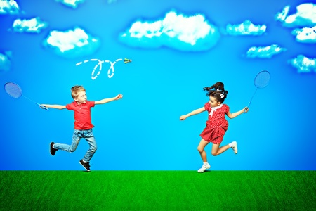 Two happy children playing badminton together over blue sky in a bright summer day. photo