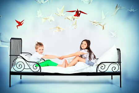 Cute kids sitting together on the bed under the blanket. Dream world. photo