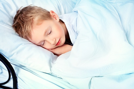 Cute little boy sleeping in a bed.  photo