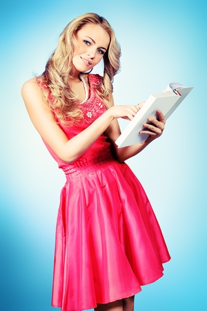 Pretty blonde woman with a book posing at studio over grey background. Stock Photo - 21199139