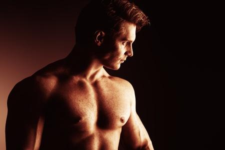 male torso: Portrait of a handsome muscular bodybuilder posing over black background. Stock Photo