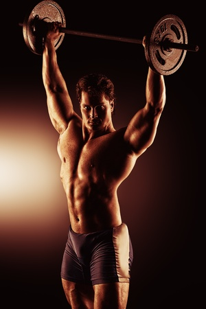 heavy weight: Portrait of a handsome muscular bodybuilder posing over black background. Stock Photo