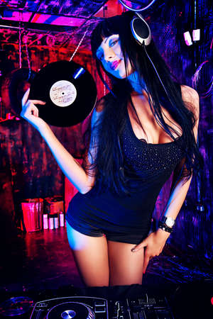 dancing: Beautiful sexy DJ girl working on a party in the old garage. Stock Photo