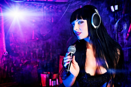 Beautiful sexy girl singing on a party in the old garage. photo