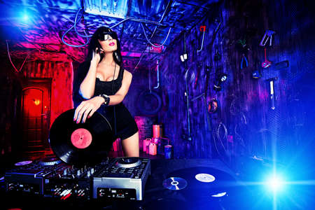 lights on: Beautiful sexy DJ girl working on a party in the old garage. Stock Photo