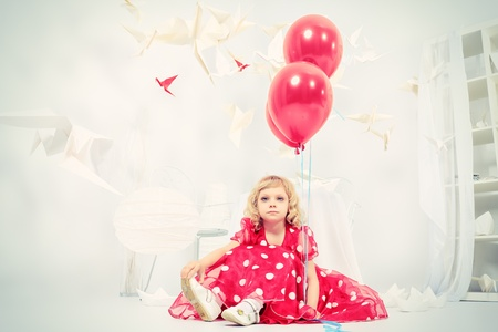 Cute little girl sitting with red balloons in a white room surrounded with paper birds.  photo