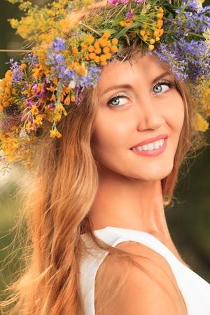circlet: Ritratto di una romantica giovane donna sorridente in una coroncina di fiori all'aperto. Archivio Fotografico