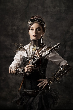 Portrait of a beautiful steampunk woman holding a gun over grunge background. photo