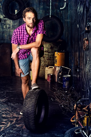 workbench: Young handsome man in the old garage. Stock Photo