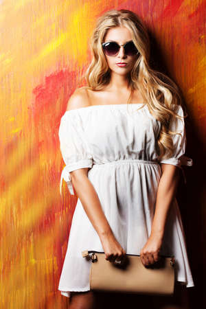 Charming blonde girl in romantic white dress and sunglasses over vivid background. Stockfoto