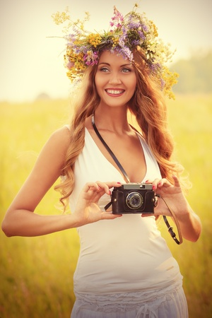 alluring: Portrait of a romantic smiling young woman in a circlet of flowers standing with her old camera outdoors. Stock Photo