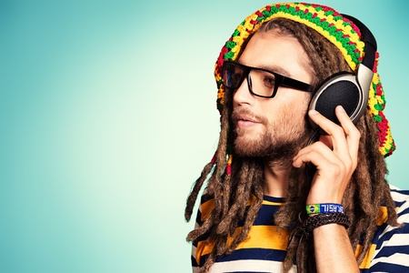 reggae: Portrait d'un heureux rastafari jeune homme �coute de la musique dans les �couteurs.