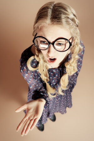 strict: Portrait of a funny blonde girl in big round spectacles posing at studio. Retro style. Stock Photo