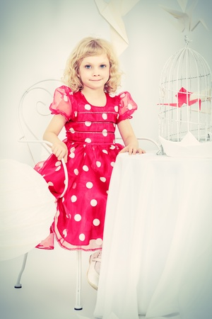Beautiful little girl dreaming with her red paper bird in a birdcage. photo