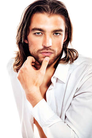 the seducer: Portrait of a handsome man in an unbuttoned white shirt. Isolated over white. Stock Photo