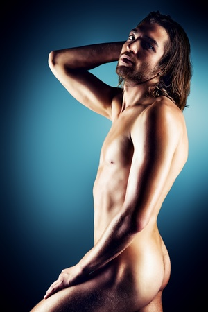Sexual muscular nude man posing over dark background. photo