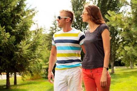 Beautiful happy couple walking in the park in sunny summer day. photo