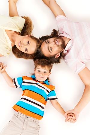 familia unida: Familia feliz acostado en el piso de la cabeza a la cabeza. Padre, madre e hijo. Aislado en blanco. Foto de archivo