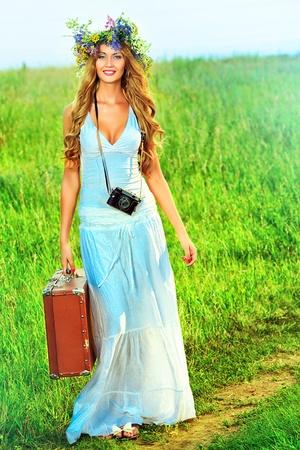 circlet: Romantico giovane donna sorridente in una coroncina di fiori va su una strada di campagna con la sua vecchia macchina fotografica e la valigia.