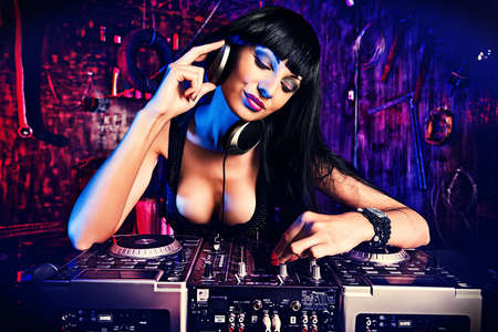 sexy headphones: Beautiful sexy DJ girl working on a party in the old garage. Stock Photo