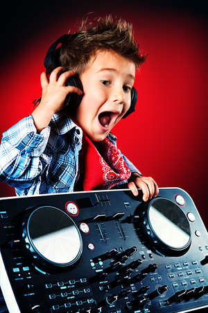 dj boy: Expressive little boy DJ in headphones mixing up some party music. Stock Photo